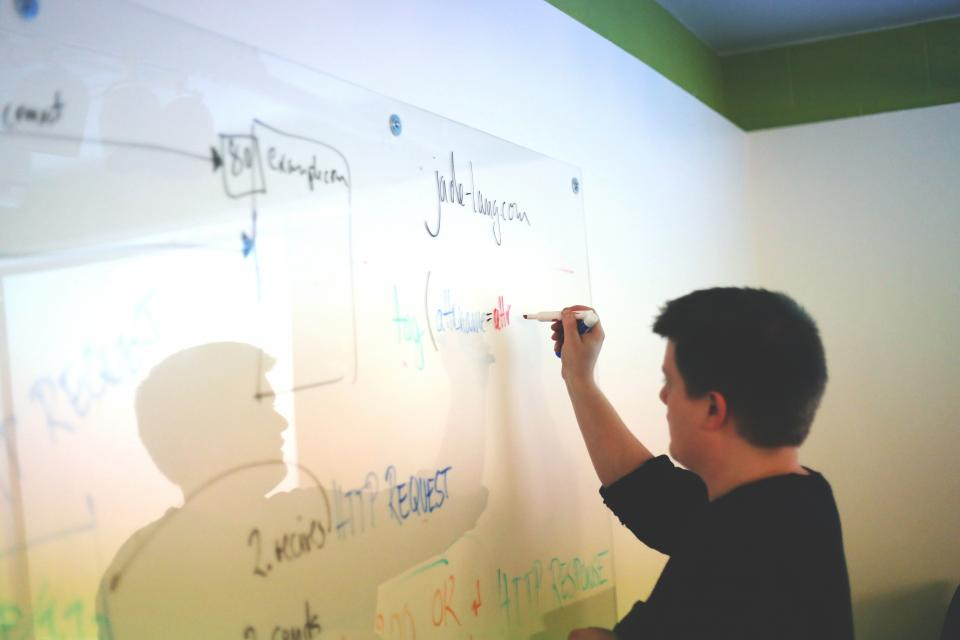 man writing online business launch plans on dry erase board