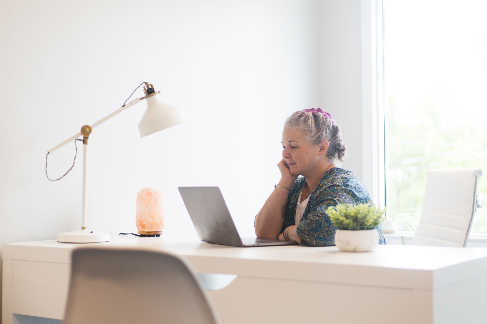 woman looking at an online business on her laptop